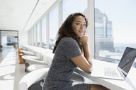 Portrait confident businesswoman at laptop in sunny urban office window - HEROF05678