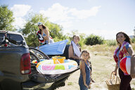 Portrait smiling family with beach equipment at sunny truck bed - HEROF05693