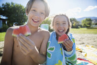 Portrait smiling brother and sister eating watermelon on sunny summer beach - HEROF05696