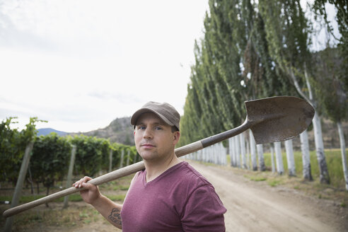 Portrait confident male worker with shovel in vineyard - HEROF05744