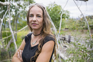 Portrait confident woman with arms crossed in vegetable garden - HEROF05789