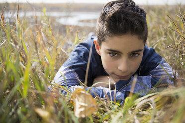 Pensive tween boy looking at autumn leaf laying in grass - HEROF05813
