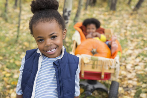 Portrait smiling girl pulling sister and autumn pumpkins in wagon - HEROF05822