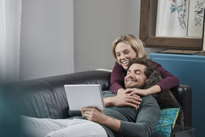 Happy couple with tablet on couch at home - RORF01570