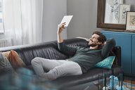 Smiling man with tablet lying on couch at home - RORF01576