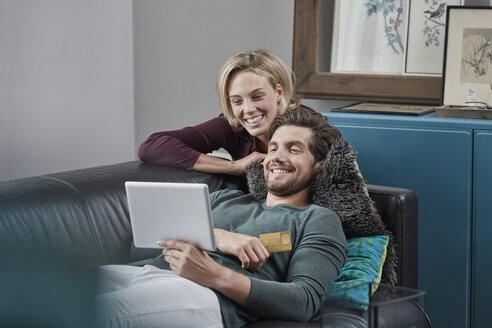 Deutschland, Nordrhein-Westfalen, Stadt Essen, Familie, Lifestyle, Paar mit Tabletcomputer auf dem Sofa, Kreditkarte, Internet-Shopping, Online-Banking, Wohnzimmer - RORF01579