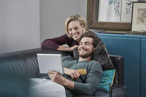 Happy couple with tablet on couch at home - RORF01579
