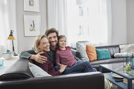 Portrait of happy family sitting on couch at home - RORF01582