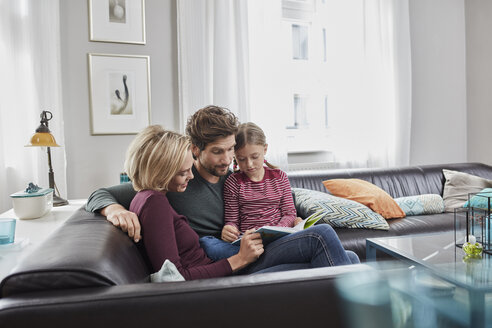 Family sitting on couch at home reading book together - RORF01585
