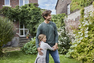Smiling father with daughter standing in garden of their home - RORF01600
