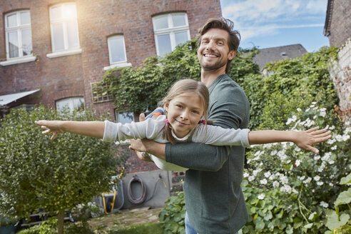 Happy father playing with daughter in garden of their home - RORF01603