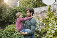Father carrying daughter in garden of their home - RORF01606
