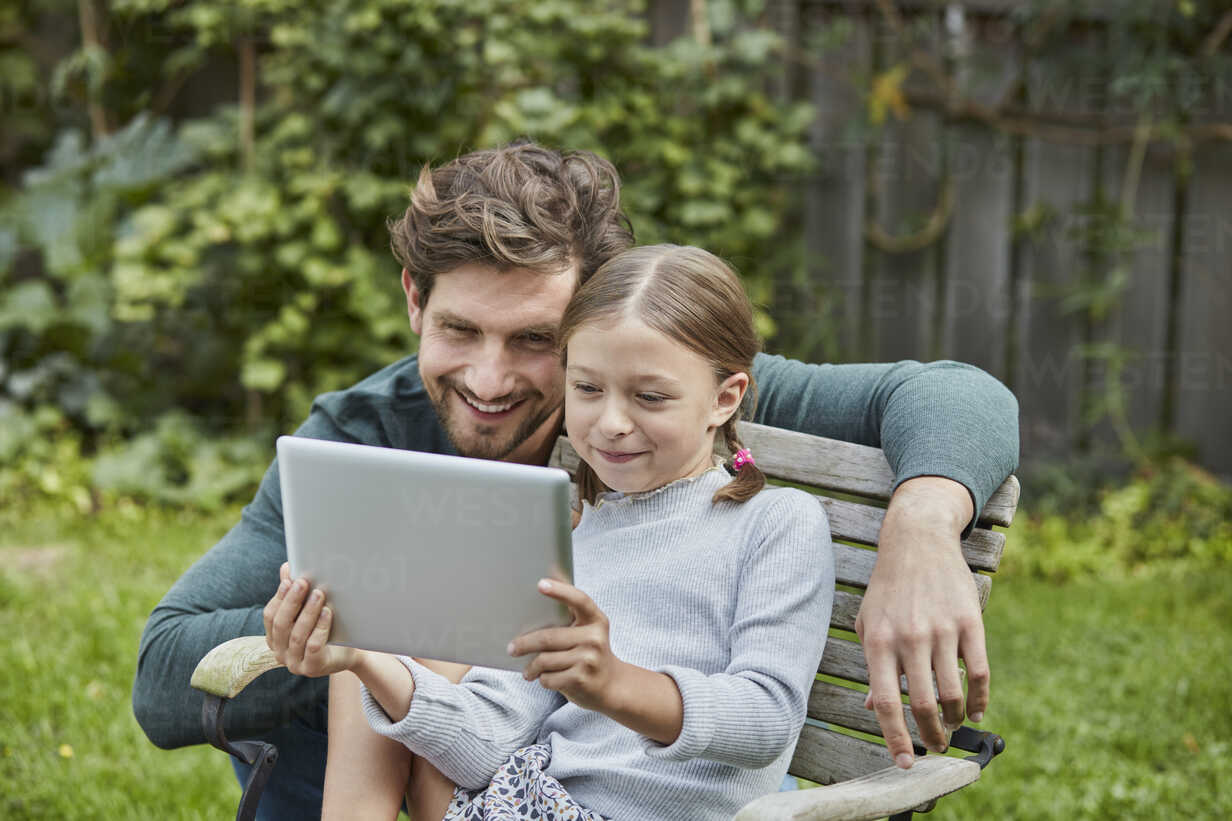 Happy father and daughter using tablet together in garden - RORF01609 - Roger Richter/Westend61