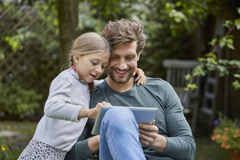 Happy father and daughter using tablet together in garden - RORF01612