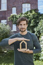 Portrait of confident man in front of his home holding house model - RORF01615