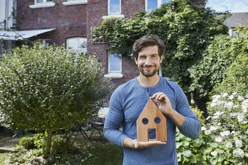 Deutschland, Nordrhein-Westfalen, Stadt Essen, Familie, Lifestyle, Mann vor Backsteinhaus mit Immobilien-Model, Haus, Immobilie - RORF01618