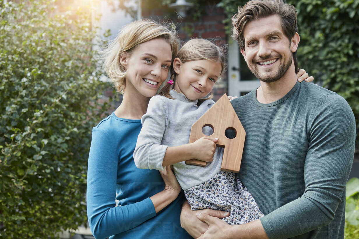 Portrait of happy family in front of their home with house model - RORF01621 - Roger Richter/Westend61