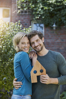 Portrait of happy couple in front of their home with house model - RORF01627
