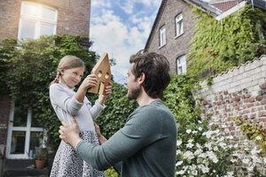 Father and daughter in garden of their home with house model - RORF01630