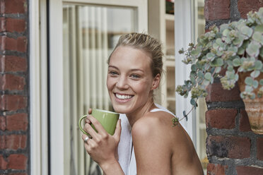 Portrait of smiling sporty young woman with cup of coffee at house entrance - RORF01642