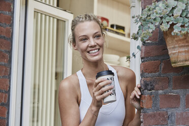 Happy sporty young woman with takeaway drink at house entrance - RORF01645