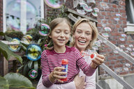 Happy mother and daughter making soap bubbles - RORF01651