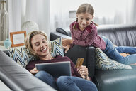 Happy mother and daughter shopping online on couch at home - RORF01654