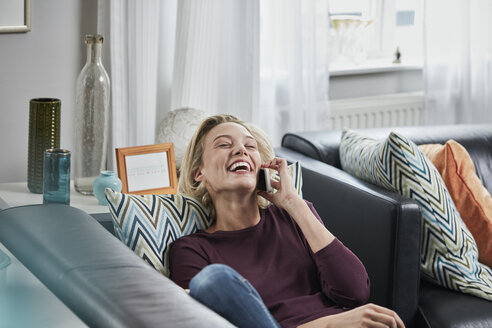 Laughing young woman on cell phone lying on couch at home - RORF01657