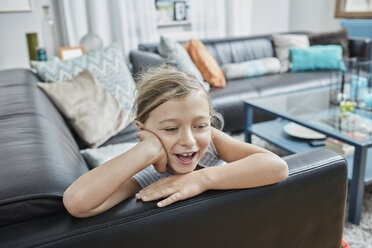 Happy girl lying on couch at home - RORF01663