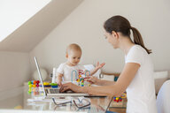Mother using laptop and little daughter playing at table at home - DIGF05615