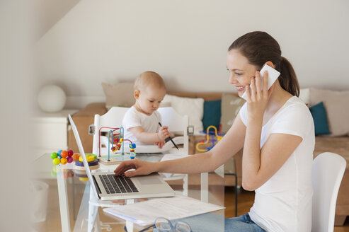 Smiling mother using laptop and cell phone with little daughter playing at table at home - DIGF05618