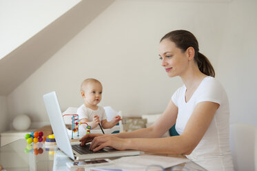 Smiling mother using laptop and little daughter playing at table at home - DIGF05621