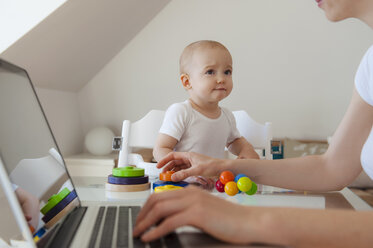 Little daughter watching mother using laptop at table at home - DIGF05624