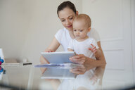 Mother and little daughter using tablet together at home - DIGF05633