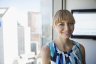 Portrait smiling woman at urban window - HEROF05893