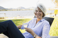 Portrait smiling woman drinking white wine at lakeside patio - HEROF05938