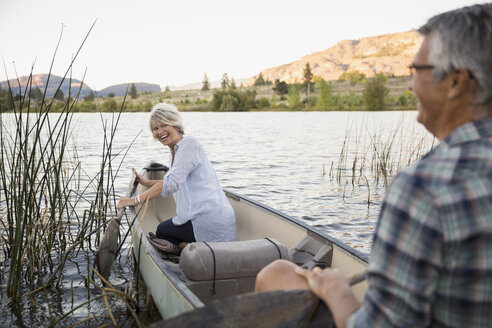 Retired couple laughing and canoeing on tranquil lake - HEROF05950