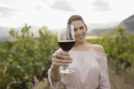 Portrait smiling woman wine tasting drinking red wine in vineyard - HEROF06010