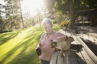 Senior woman petting cat and drinking coffee on sunny, idyllic patio - HEROF06022