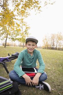 Portrait smiling tween boy with digital tablet in autumn park - HEROF06034