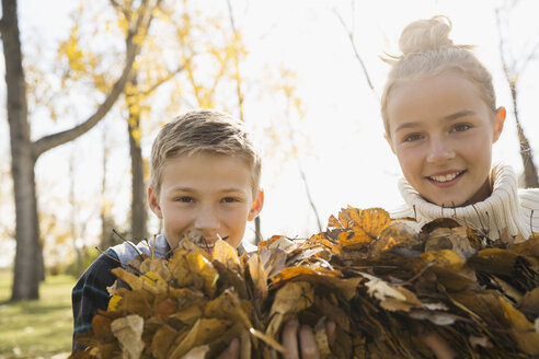 Portrait smiling tween boy and girl holding autumn leaves in park - HEROF06046