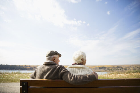 Senior couple sitting on bench looking at sunny autumn view - HEROF06061