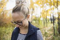 Smiling blonde woman looking down in autumn woods - HEROF06076