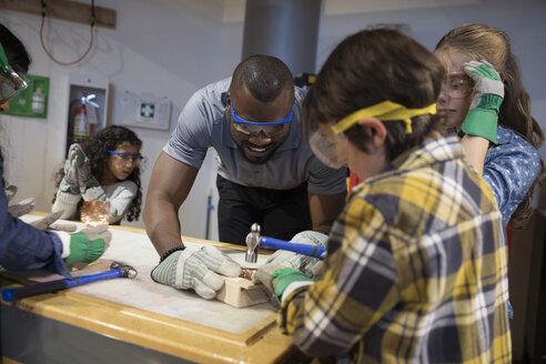 Scientist and children hammering wood in science center - HEROF06100
