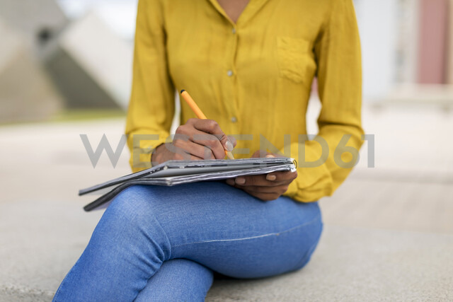 Woman sitting on bench taking notes, partial view - MAUF02325 - Mauro Grigollo/Westend61