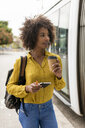 Portrait of smiling woman with coffee to go and notebook in the city - MAUF02331