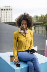 Woman sitting on bench with coffee to go and notebook looking at smartphone - MAUF02334