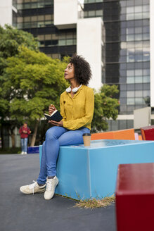Woman sitting on bench with smartphone and coffee writing in notebook - MAUF02337
