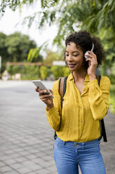 Smiling woman listening music with headphones and smartphone outdoors - MAUF02340