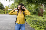 Happy woman listening music with headphones outdoors - MAUF02343